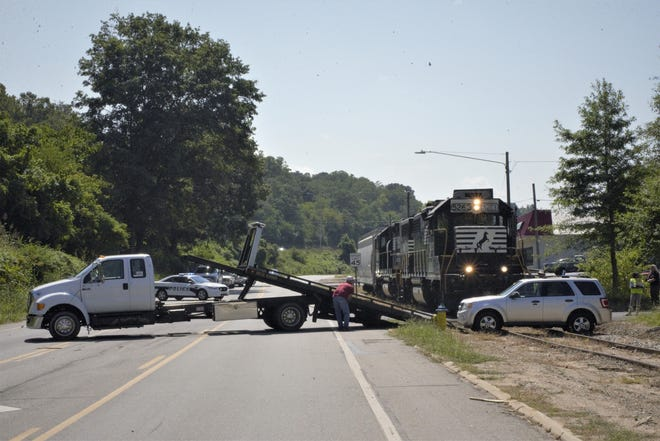 Authorities work to remove a vehicle that was struck by a train from a set of train tracks that runs along Riverside Drive.