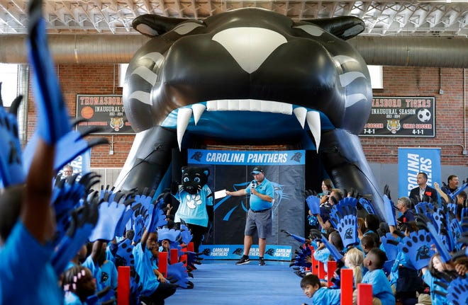 """Carolina Panthers owner David Tepper speaks to students during a """"kickoff rally"""" at Thomasboro Academy in Charlotte, N.C., on Aug. 28, 2018. Tepper's charitable foundation along with several players groups and other partners will provide 12,000 backpacks full of supplies to 17 elementary schools in Charlotte-Mecklenburg Schools, as well as an additional school in Kannapolis City Schools."""