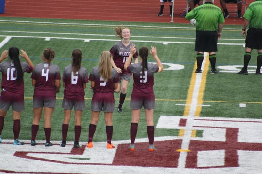 Liz Akulis (number 11) runs on the field to high-five Olivia Bowman (number 3).