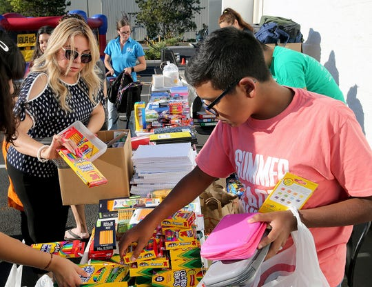 Martitha May, left, and Manny Tovar, 14, put out school supplies for children at the Newlife training center in Silverdale on Monday. The event was aimed at the Spanish-speaking community, providing backpacks filled with school supplies for every child in attendance.