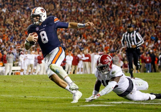 FILE-In this Nov. 25, 2017, file photo, Auburn quarterback Jarrett Stidham (8) gets past Alabama linebacker Dylan Moses (18) to carry the ball in for a touchdown during the second half of the Iron Bowl NCAA college football game, in Auburn, Ala. Auburn has high hopes for Stidham, who was one of the SEC's most efficient passers as a first-year starter. Auburn hasn't had a two-year starter at quarterback since Nick Marshall in 2013 and 2014.  (AP Photo/Butch Dill, File)