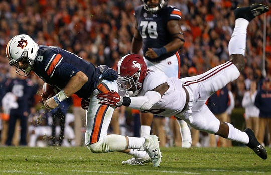 Auburn quarterback Jarrett Stidham tries to evade the grasp of Alabama's Hootie Jones during the Iron Bowl last November. Stidham's ability to gain yards with both his arm and his legs has the full attention of the Washington Huskies.