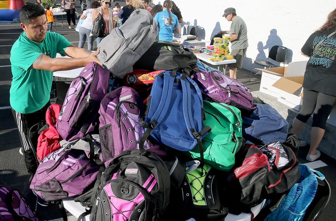 Rene Tovar makes a mountain of backpacks full of school supplies for children at the Newlife training center in Silverdale on Monday. Newlife has been trying to build bridges to the Spanish-speaking community.