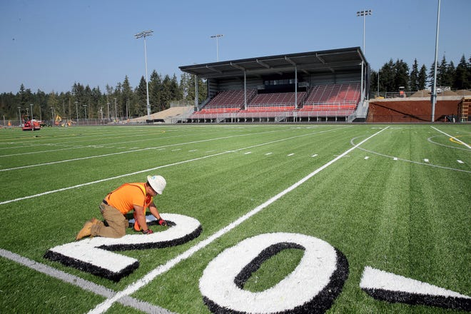 Angel Freed of Sprint Turf works on the new turf field at Central Kitsap High School on Tuesday. Kitsap Credit Union is paying for naming rights on the new stadium, and the sponsorship will pay for bleachers.