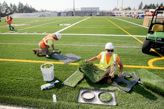 Chance Hall , center, and Greg Martin of Sprint Turf lay down turf on the new athletic field at Central Kitsap High School on Tuesday.