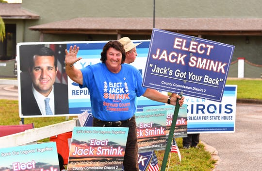 Democratic District 2 County Commission candidate Jack Smink waves to voters outside the polling site at the Moose Lodge on Merritt Island.