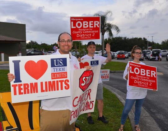 Bryan Lober, who was out campaigning all day at the Moose Lodge on Merritt Island, finishes up the day waving at voters with Nick and Hannah Tomboulides. Candidates and supporters were out  all day Tuesday waving signs  and waving to voters at polling sites around the county.