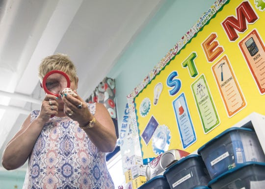 Bishop Flaget pre-school teacher Kim Leeth looks at a crab through a magnifying glass that is used to teach students about life science.