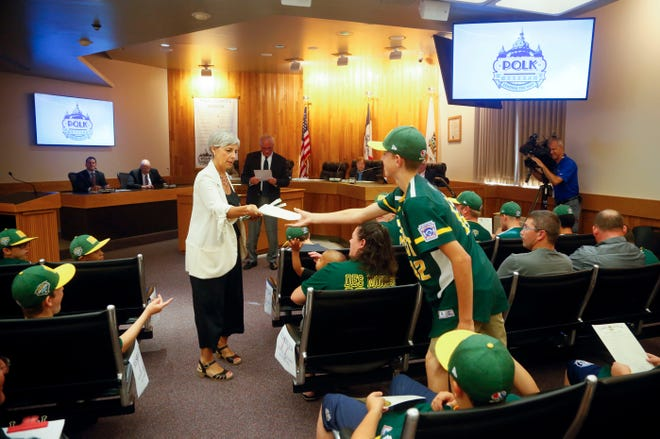 Polk County Supervisors Angela Connolly hands out copies of a proclamation recognizing the Grand View Little League team for reaching the Little League World Series to players in August.