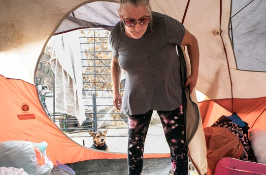 Lynn Adams, 61, who is uninsured, lost the home she was renting with her family and pets during the Carr fire in July and now lives in a tent on the property in Redding, Calif., Saturday, August 26, 2018. Most of her pets are at Haven Animal Shelter while she and dog Scamp look for a place to rent that allows animals.