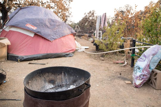 Lynn Adams, 61, lost the home she was renting on Cactus Lane during the Carr fire in July and is living in a tent cooking with an open fire on the property in Redding, Calif., Saturday, August 26, 2018.