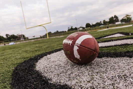 Football lays on the field, high school football