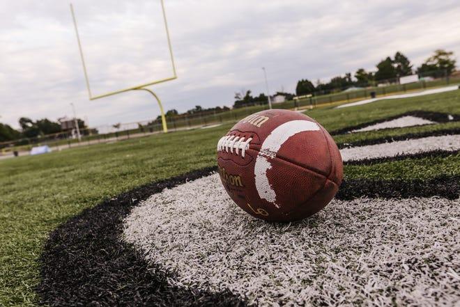 A football lays on a high school football field.