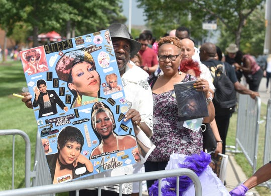 James Brooks of Detroit holds his custom photo montage outside the Charles Wright Museum of African-American History as people prepare to pay their respects to Aretha Franklin.