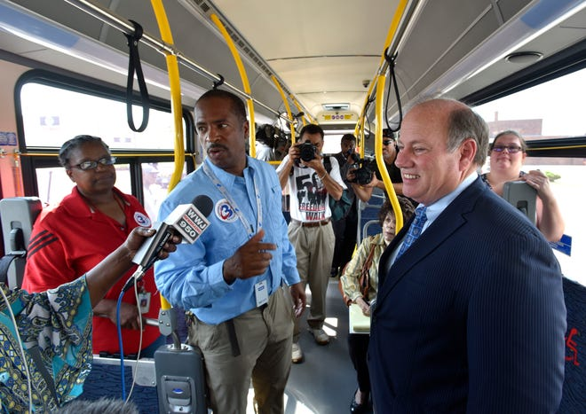 Councilman Scott Benson, left, and Mayor Mike Duggan, right, answer reporters' questions on board one of the ConnectTen buses.