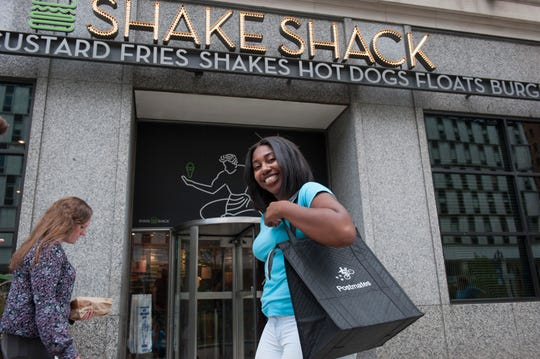 Postmates driver Erica Carter, seen outside Shake Shack in downtown Detroit in 2018.
