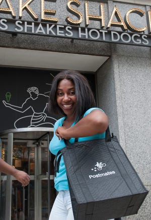 Postmates driver Erica Carter, seen here outside Shake Shack in Downtown Detroit, has been picking up meals at area restaurants and delivering them to customers for just a few weeks.