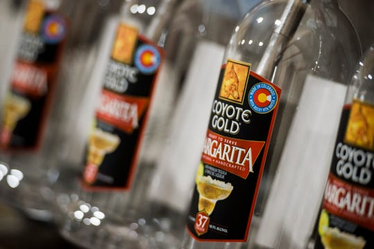 """Empty Coyote Gold margarita bottles sit on """"Bessy"""" the filler while Maureen """"Mo"""" Schaffer and Randy Zwetzig give a rundown of how they manufacture their margaritas on Tuesday, Aug. 28, 2018, at Coyote Gold's manufacturing plant in Fort Collins, Colo."""
