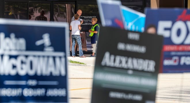 An official talks to a couple before they enter to vote. The Lee County Elections Center was a hopping place over the lunch hour. Voting for the primary has begun.