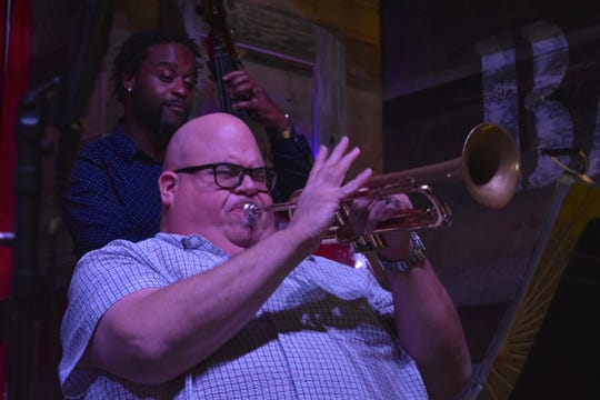 Trumpeter Dan Miller blasts out a jazz solo at The Barrel Room while bassist Brandon L. Robertson looks on approvingly.