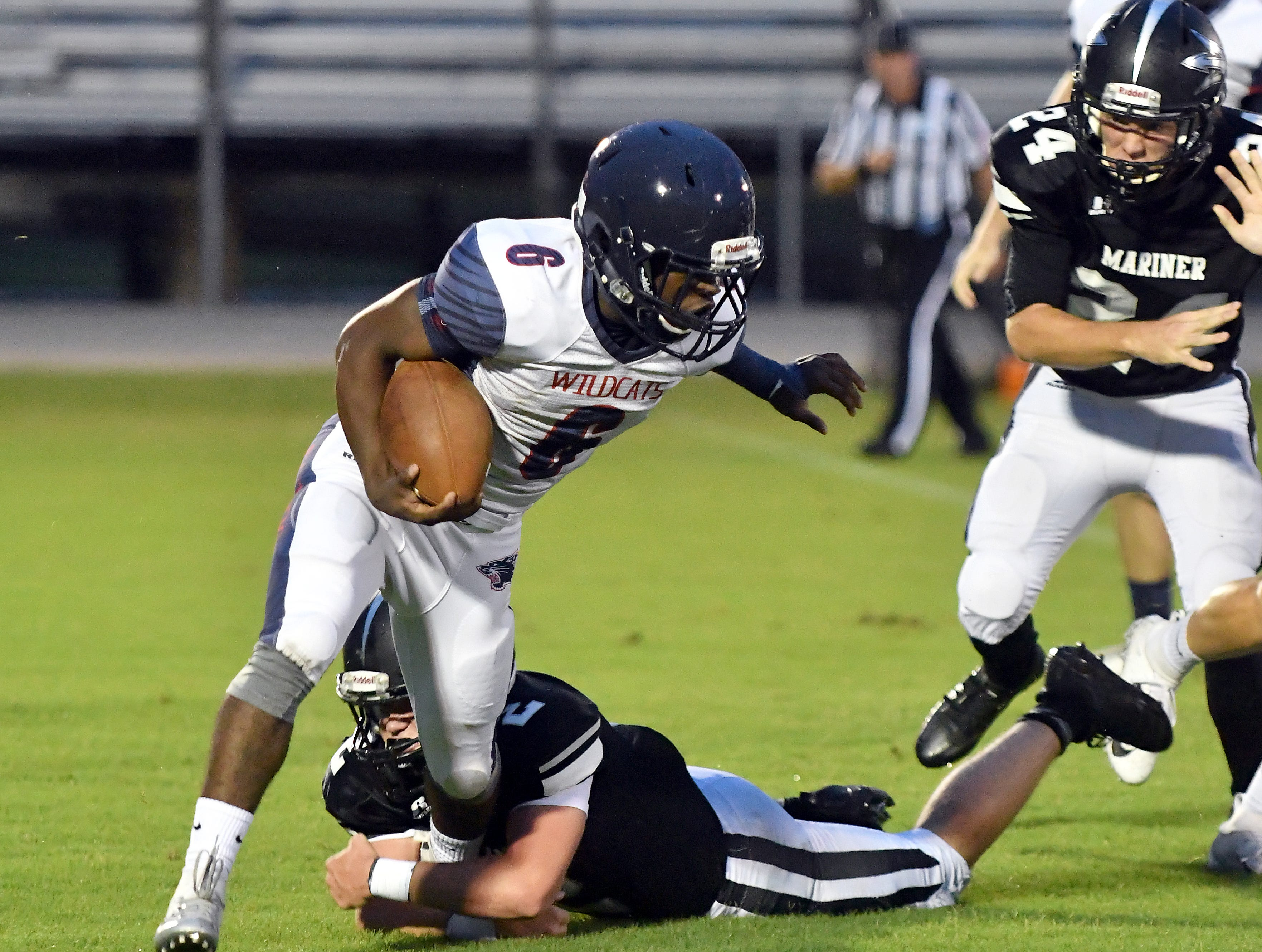 Estero High School running back Derrick Peart (6) tries block a Mariner High School defender during thier game in Cape Coral Monday, Aug. 27, 2018.