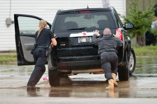 A Green Bay police officer helps a motorist push a stranded car from Main Street on the east side of Green Bay in fierce storms