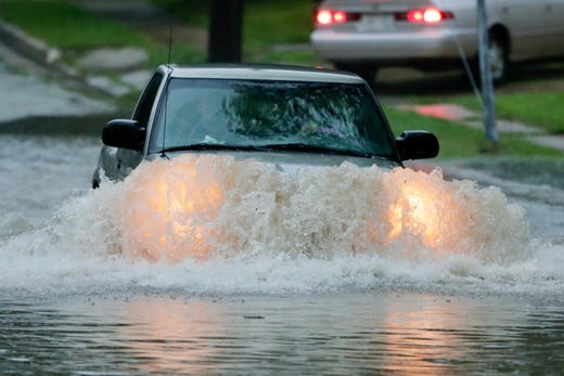The driver of a small truck picks up the brave Tuesday in Oakland Street on the east side of Green Bay. Heavy rains caused flooding and traffic problems throughout Northeast Wisconsin