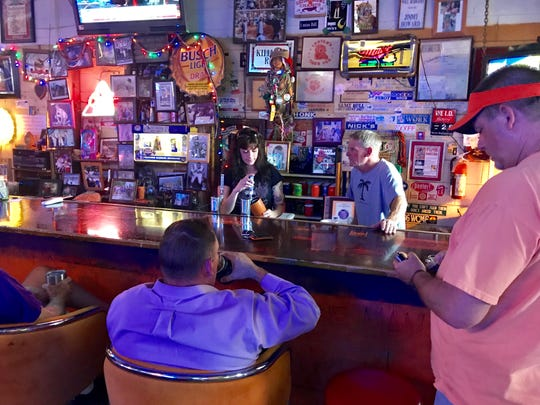 The regulars gather round to talk football with Jimmy Howard, owner of Sloan Street Tap Room in Clemson.