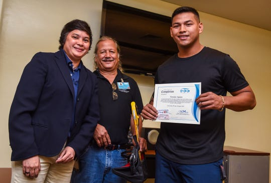 Terence Aguon, right, receives his certificate of completion for the Guam Community College's Future Builders of Guam Construction Boot Camp on August 28, 2018.