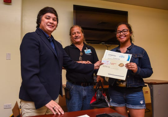 Savannah Tigil, right, receives her certificate of completion for the Guam Community College's Future Builders of Guam Construction Boot Camp during a brief ceremony at the learning institution in Mangilao on Tuesday, Aug. 28, 2018. Program participants trained for six weeks, in classroom and lab environments, to learn the construction fields of carpentry, welding, electrical, masonry, and plumbing, said Pilar Williams, GCC School of Trades and Professional Services associate dean.