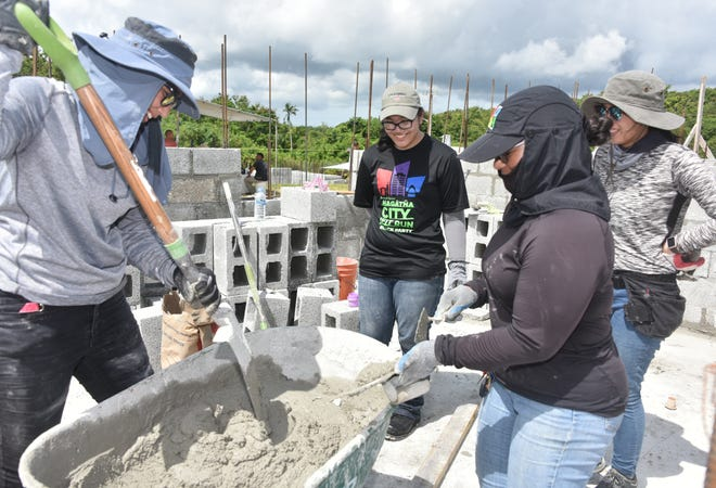Future homeowners Laura Fernandez, left, Tracy Cantimbuhan, back right, and Rita Cepeda, front right, and volunteer Camarin Borja, center, work on Cepeda's house under construction in Mangilao on Aug. 12, 2018.