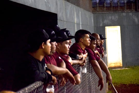 Yigo Astros players get up and close during the final inning of their playoff game against the Autospot Orioles Tuesday night at the Paseo Stadium.