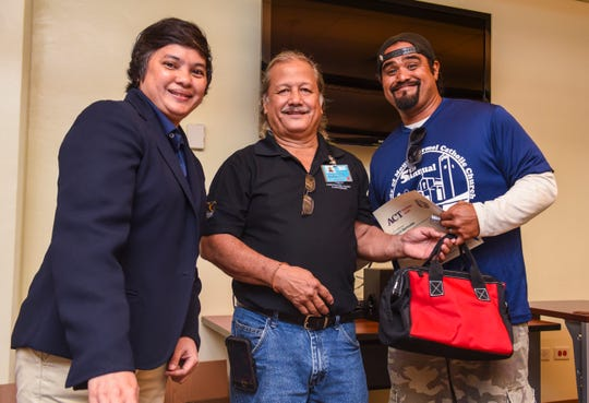 Jason Bermudes, right, receives his certificate of completion for the Guam Community College's Future Builders of Guam Construction Boot Camp during a brief ceremony at the learning institution in Mangilao on Tuesday, Aug. 28, 2018. Program participants trained for six weeks, in classroom and lab environments, to learn the construction fields of carpentry, welding, electrical, masonry, and plumbing, said Pilar Williams, GCC School of Trades and Professional Services associate dean.