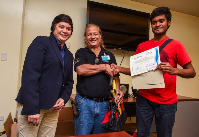 Rico Wasisang, right, receives his certificate of completion for the Guam Community College's Future Builders of Guam Construction Boot Camp during a brief ceremony at the learning institution in Mangilao on Tuesday, Aug. 28, 2018. Program participants trained for six weeks, in classroom and lab environments, to learn the construction fields of carpentry, welding, electrical, masonry, and plumbing, said Pilar Williams, GCC School of Trades and Professional Services associate dean.