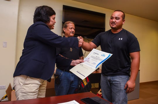 Barry Toves, right, receives his certificate of completion for the Guam Community College's Future Builders of Guam Construction Boot Camp during a brief ceremony at the learning institution in Mangilao on Tuesday, Aug. 28, 2018. Program participants trained for six weeks, in classroom and lab environments, to learn the construction fields of carpentry, welding, electrical, masonry, and plumbing, said Pilar Williams, GCC School of Trades and Professional Services associate dean.