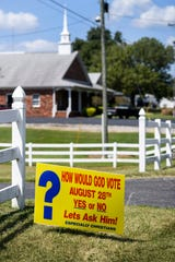 "A sign that says ""How would God vote, August 28th, yes or no? Let's ask him,"" is seen along the side of the road near Bellfield Baptist Church, the Anthoston voting precinct polling place, in Henderson County Tuesday. Registered voters were asked if they were or were not in favor of the sale of alcoholic beverages at small farm wineries."