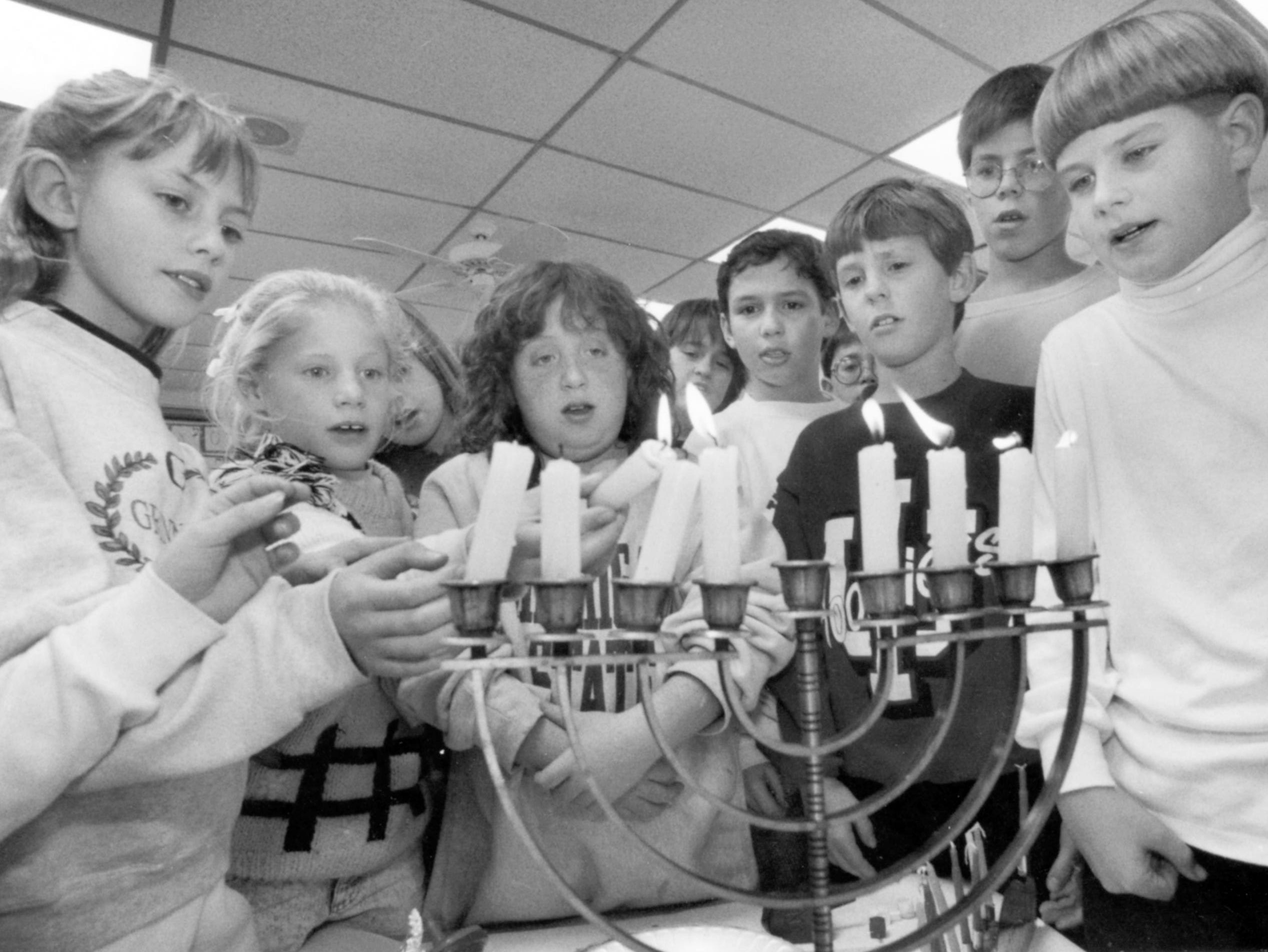 Pupils in Rachel Englemayer's class at the Board of Jewish Education practice lighting the menorah while saying the Hanukkah prayer on Dec. 26, 1991.