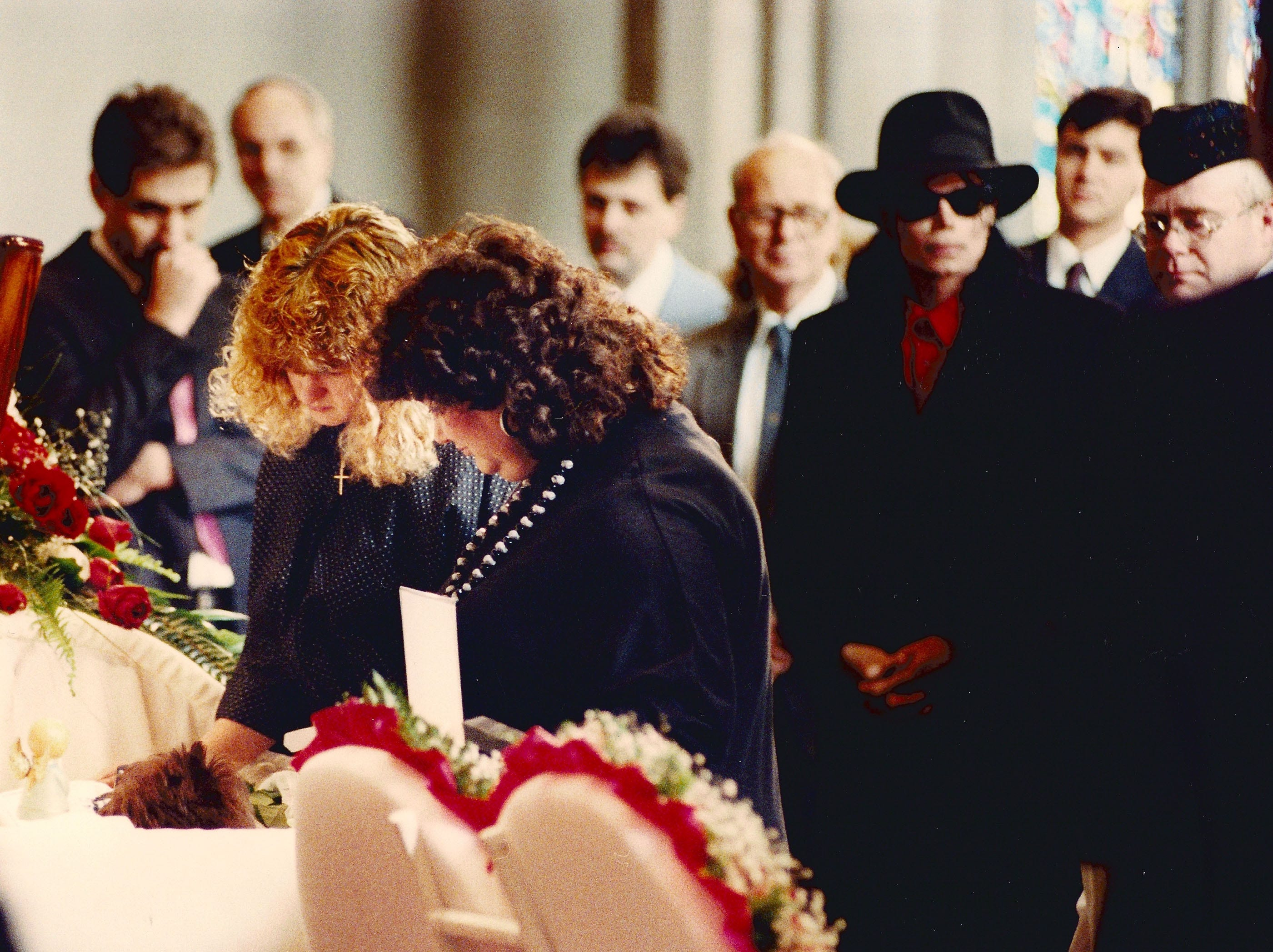 Michael Jackson and Elton John stand behind Jeanne White and daughter Andrea as they view the body of Ryan White April 11, 1990