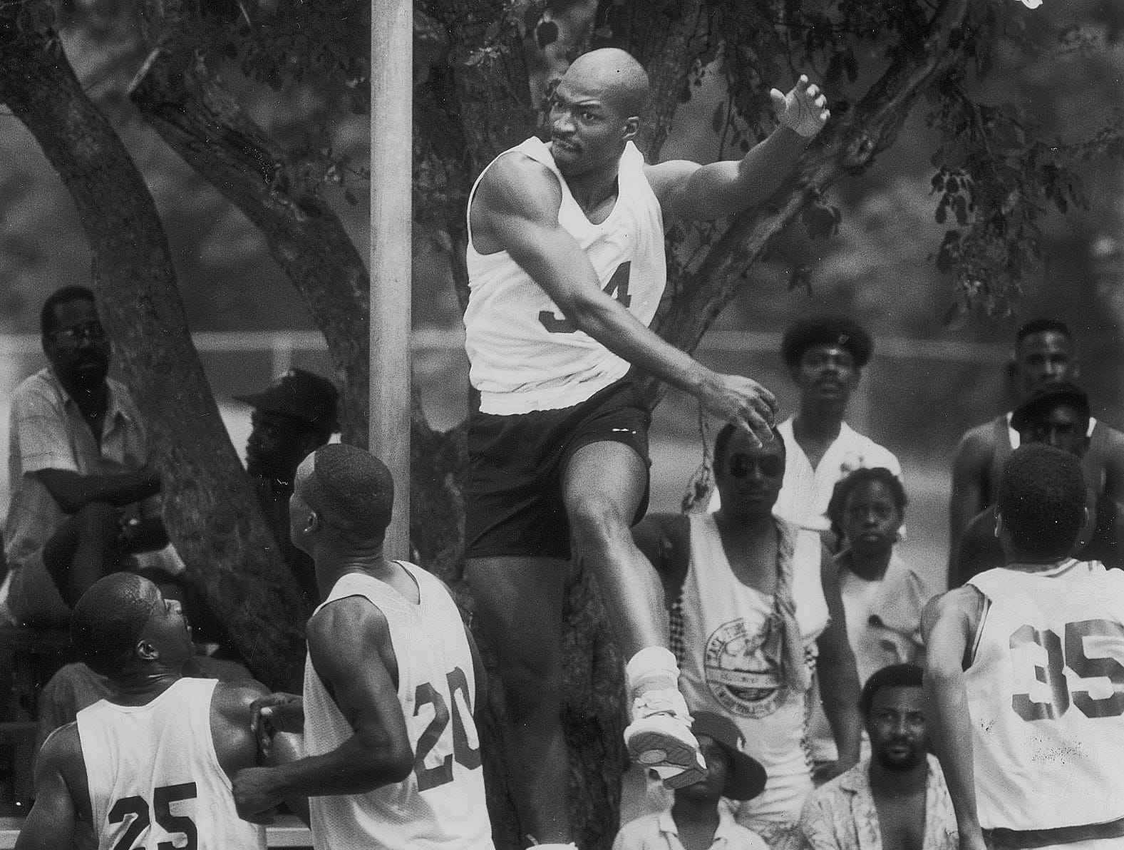 Jerome Brewer leaps high into the air and swats a shot away in a basketball game at Washington Park sponsored by the Black Expo.  Hundreds of people came to enjoy the Soul Fest and Dust Bowl basketball game Jun 16, 1990.