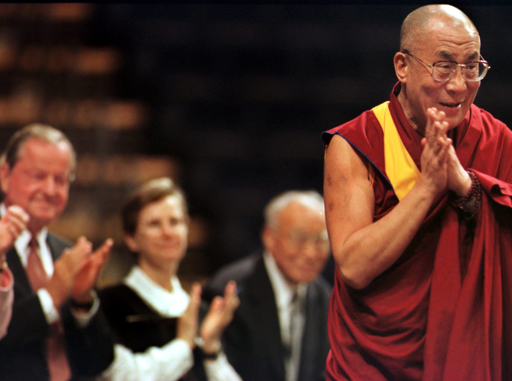 His Holiness, the Fourteenth Dalai Lama (cq, right), acknowledges the crowd at Market Square Arena, Monday, August 16, 1999, during a ceremony welcoming him to Indiana.  In the background are (from left) Governor Frank OÕBannon , Sister Mary Margaret Funk, and the Dalai LamaÕs eldest brother, Thubten Norbu.