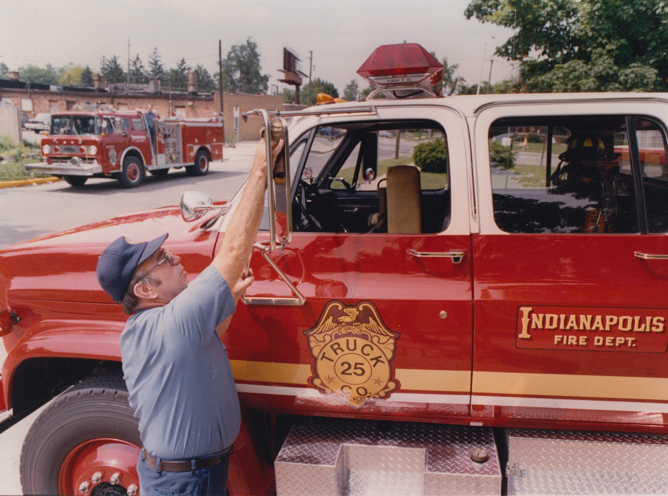 Indianapolis Fire Department engineer Ron L. Bowman polishes the cab of Truck 25 outside Station 25 on the Eastside May 28, 1990.