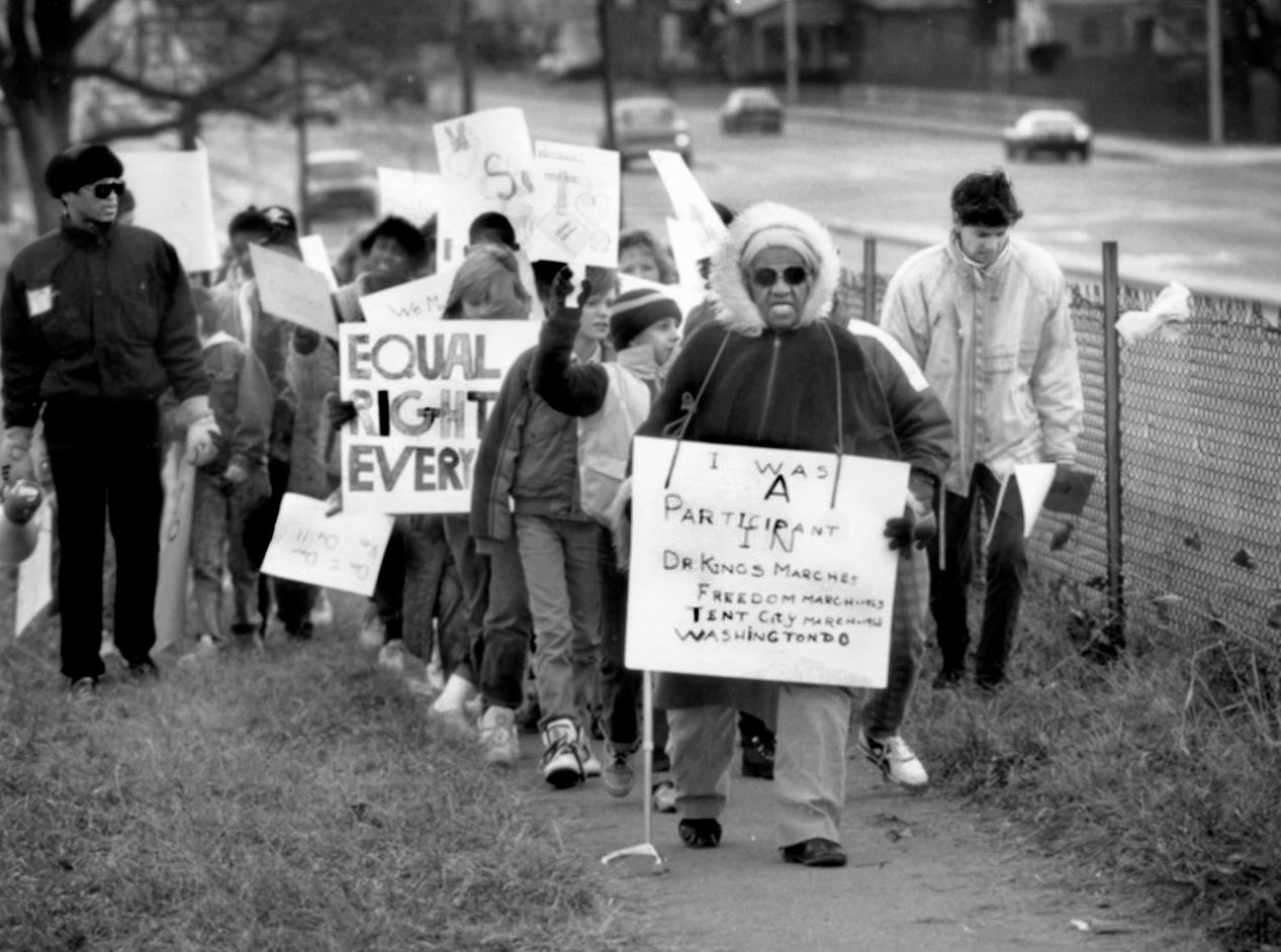 "Substitute teacher Amy Robinson, 76, led pupils from Indianapolis Public School 69 on a march in Indianapolis on Jan. 12, 1990 commemorating the 1963 March on Washington, after which the Rev. Martin Luther King Jr. gave his ""I Have a Dream"" speech. Robinson, a native of Indianapolis, carried a sign that noted her participation in two of the Rev. Martin Luther King Jr's marches."