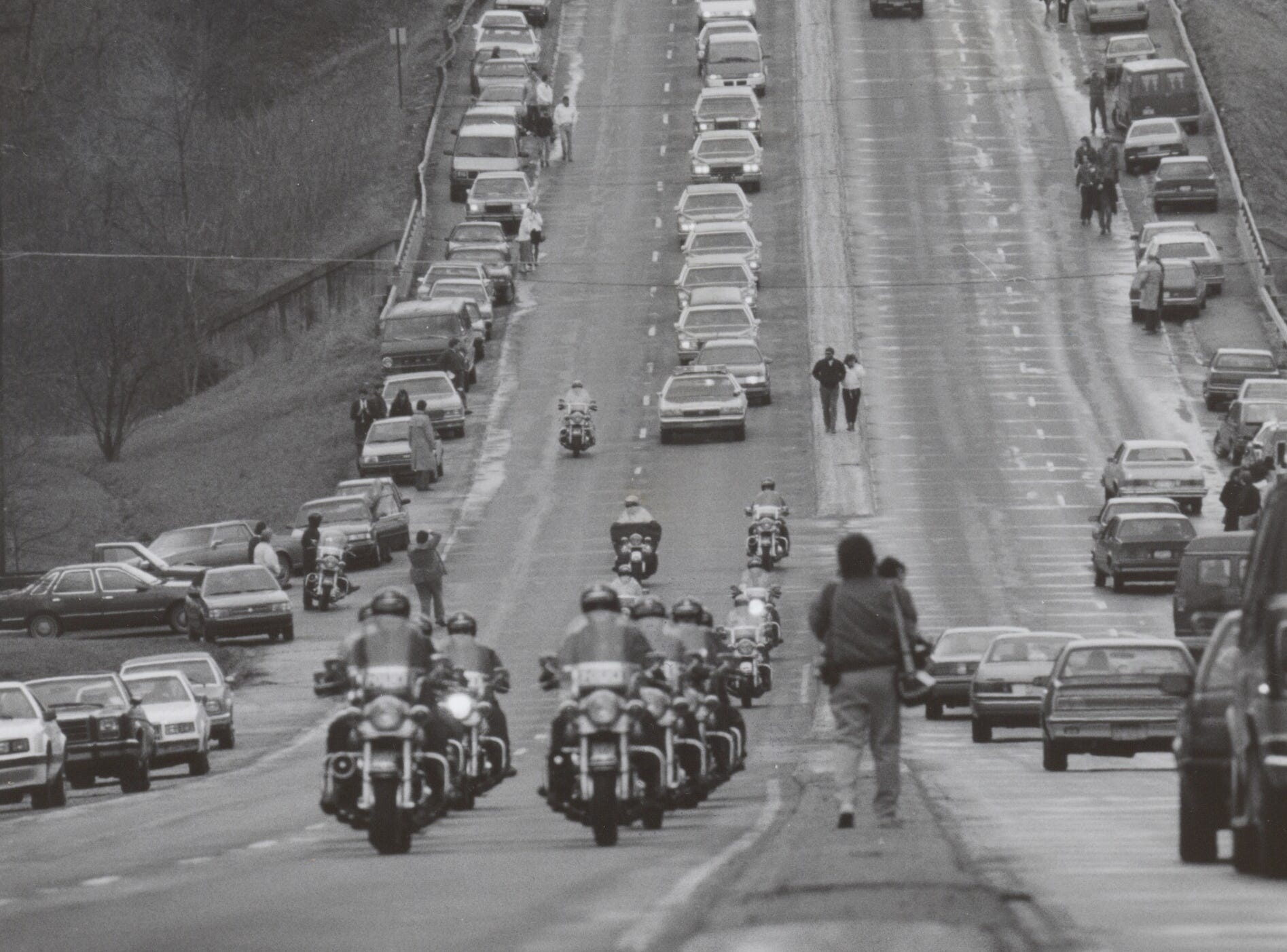 A police escort leads hundreds of cars in the funeral procession of Ryan White to the cemetery. April 11, 1990