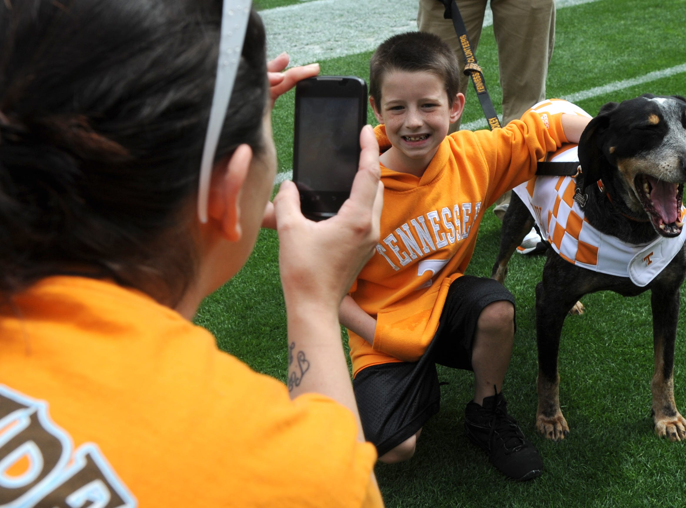Trent Pyles, center, poses with Smokey as his mother, April, takes a photo during Fan Day prior to the Orange and White Game at Neyland Stadium Saturday, April 21, 2012.