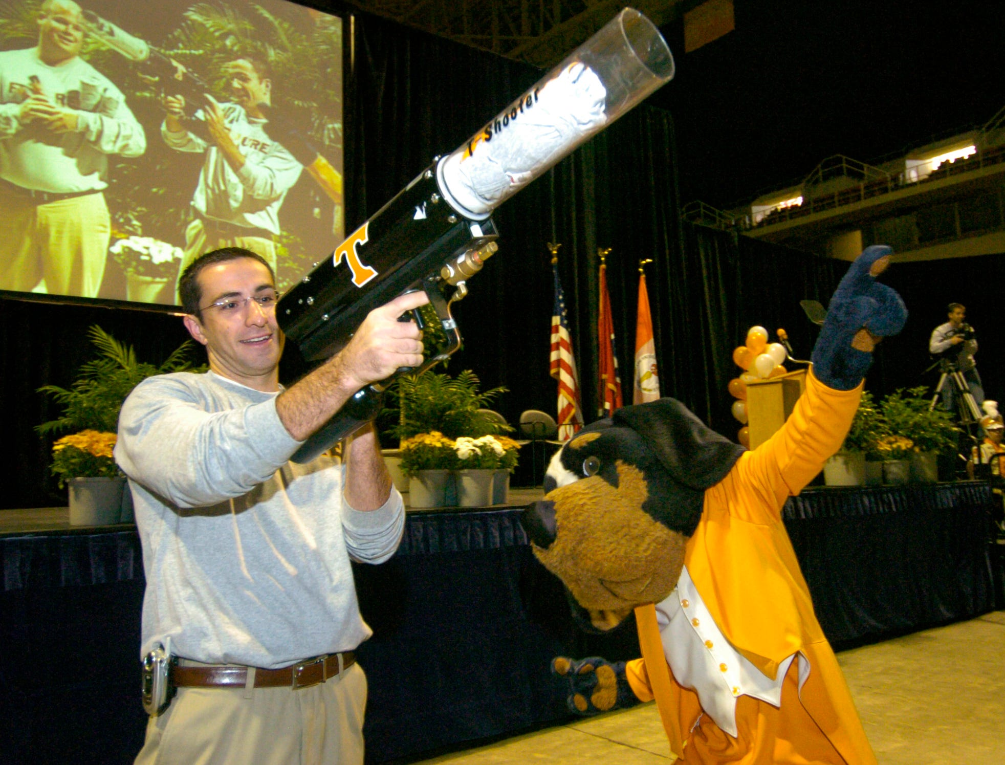 UT student Jimmy Delaney, left, waits for his gun to re-charge to launch another logo t-shirt into the crowd gathered to hear UT President John Petersen addressed all campuses via videolink from Thompson-Boling Arena Tuesday morning. Delaney along with Smokey were on hand to get the crowd of UT employees excited before the announcement of   a new marketing and branding initiative.