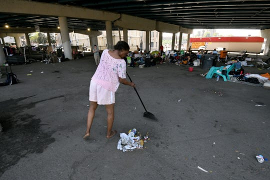 A homeless lady named Veronica, who asked to use only her first name, sweeps up her area under the Broadway viaduct under Interstate 40, where many homeless people live, on Tuesday, August 28, 2018.