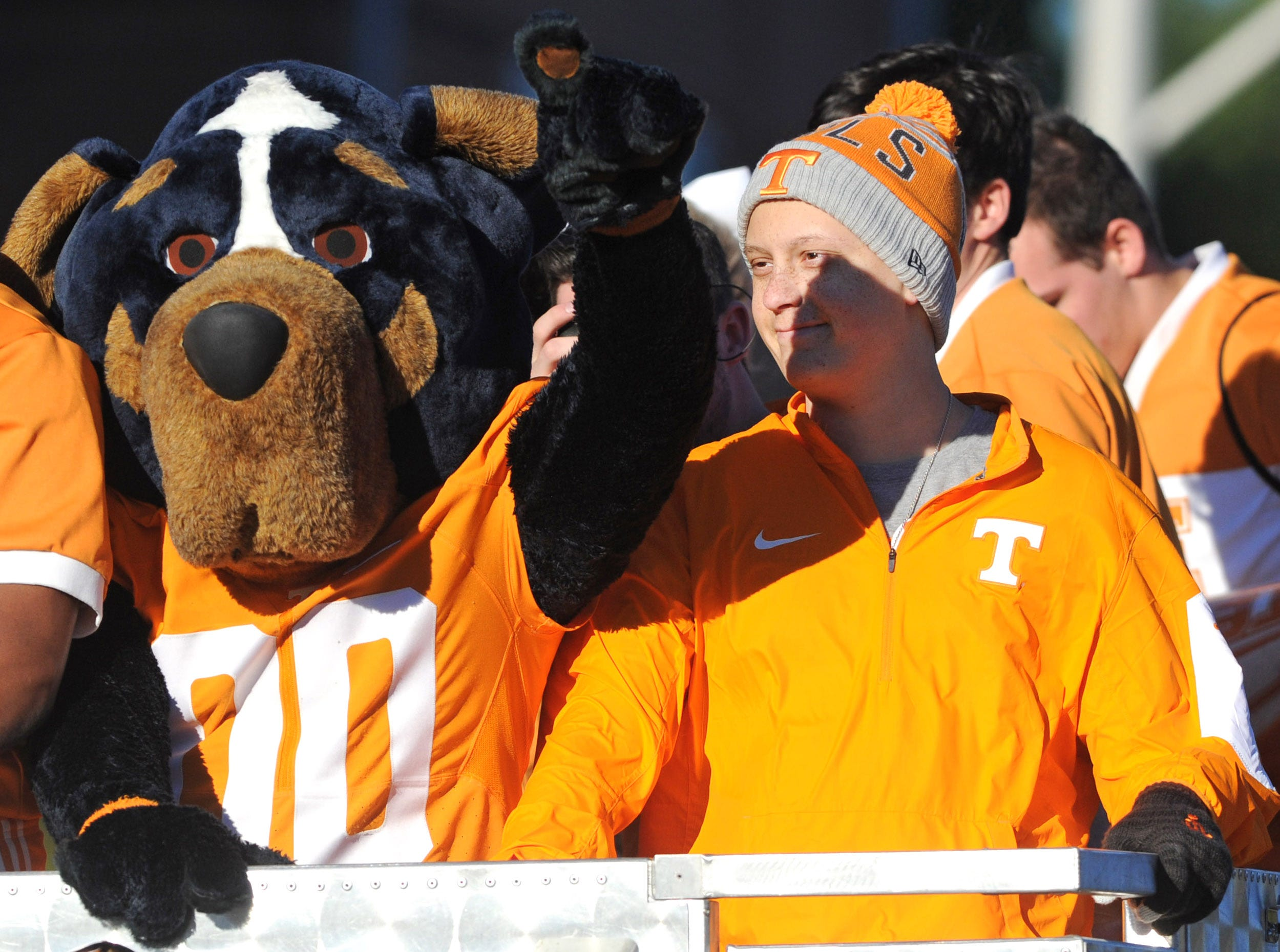 Noah Hays, 16, right, rides a fire engine with University of Tennessee mascot, Smokey, during a homecoming parade on Volunteer Blvd. in Knoxville on Friday, Nov. 13, 2015.