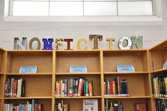 Fulton High media specialist Nichole Dossett used a variety of letter styles and mediums to create signs for the sections in the library.