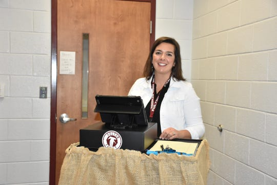 Fulton High media specialist uses a portable station to check out students for Fulton Family gear and the coffee bar.