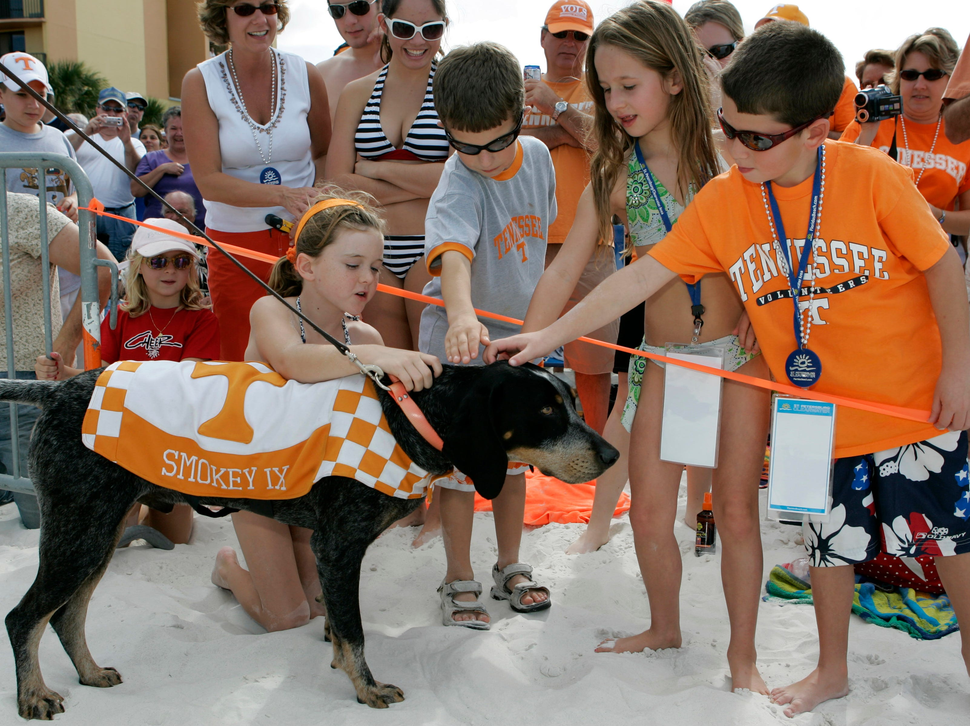 Tennessee fans, left to right, Karlie Herdson, Luke Weaver, Hannah Emery and Reece Emery pet Smokey IX, the team's mascot, during the Outback Bowl Beach Day on Saturday, Dec. 30, 2006, in Clearwater, Fla. Tennessee takes on Penn State in the Outback Bowl college football game on New Year's Day.